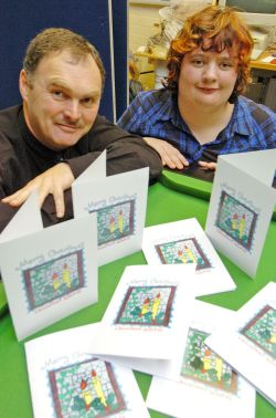 County Council Cabinet Member for Children and Young People, Councillor Huw George is pictured with Amy and her winning Christmas card design