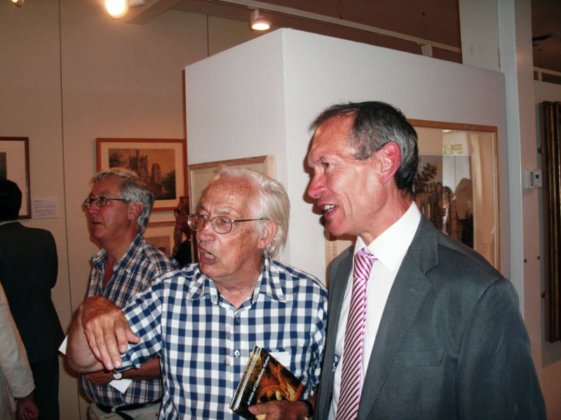 Co-curator William Gibbs discusses the paintings with Culture Minister John Griffiths AM