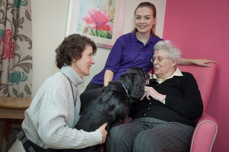 Pendine Parks Bryn Seiont Newydd in Caernarfon.. Volunteers take their Dogs in to meet residents. Pictured is Volunteer Megan Roberts Gem the working Cocker Spaniel, Nia Lloyd Roberts Artist in Residence and Enrichment Co ordinator resident Patricia Swift.