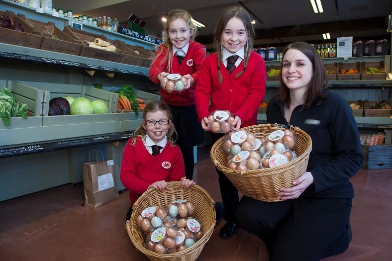BODNANT WELSH FOODS ... Ysgol Sant Sior pupils deliver their 2,000th egg. Pictured are pupils Belle Harvey,9, Lily Joe,9 and Evie Owen,9 with Farm shop supervisor at Bodnant Hayley Roberts.