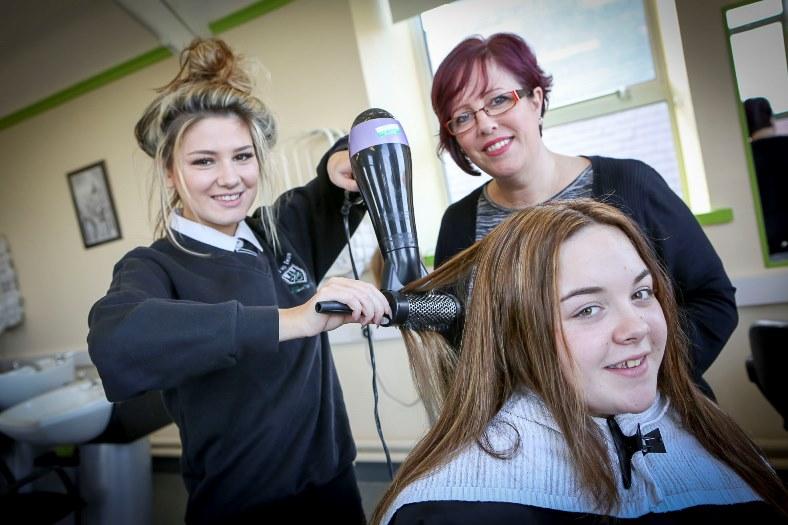 Ysgol Emrys ap Iwan, Abergele. School now has a beauty salon. Pictured: Deanna Dyson age 15 blow dries her friend Bethany Pardoe's hair age 14 with hairdressing teacher Mandy Owen