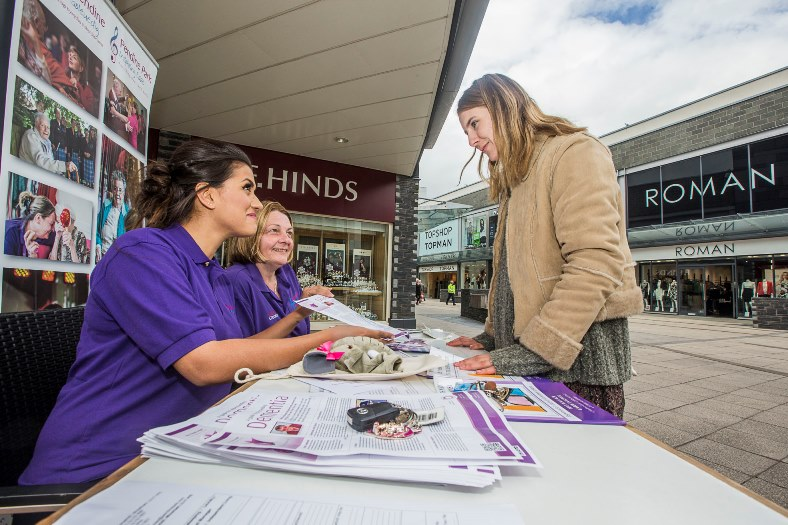 Anita Moran and Olivia Thomas from Pendine Park at an information table in Eagles Meadow, Wrexham giving out information on Dementia Awareness Week talk to Melys Edwards, from Minera