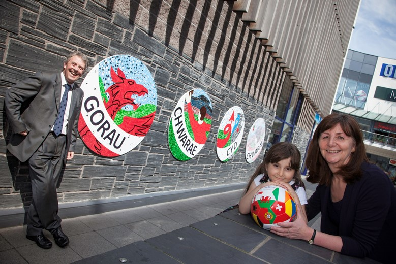 EAGLES MEADOW, WREXHAM   Kevin Critchley,   Jessica Castro,5 and  Lesley Griffiths AM  by the new collage to mark Wales's qualification for the Euro 2016 football championships.