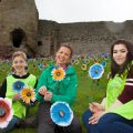 St Kentigern Hospice planted 1,000 metal flowers in the grounds of the castle as part of a public display and to form part of the Rhuddlan entry into Wales in Bloom Pictured bringing colour to t Rhuddlan Castle on a rainy day is fundraising manager Laura Parry with  Ysgol Eirias pupils Ethan Hughes and Amber Lea Powell.