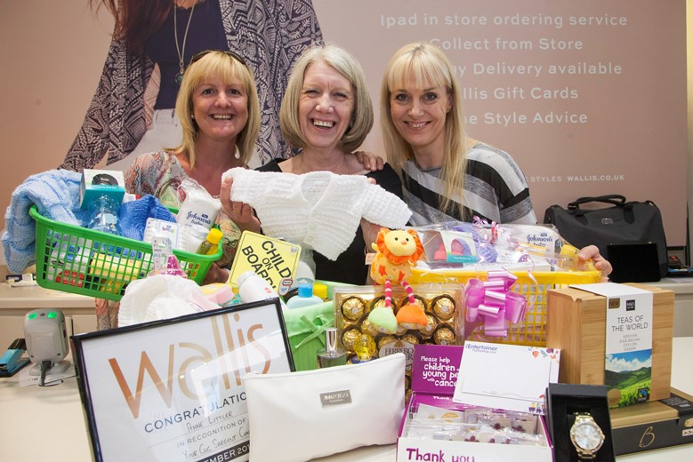 Eagles Meadow....  Pictured are Lisa Jones, Wallis  Manager Ann Littler  and Lisa Varelo Pinto with some of the  prizes in the grand raffle they're doing in June in aid of CLIC Sargent children's cancer charity.