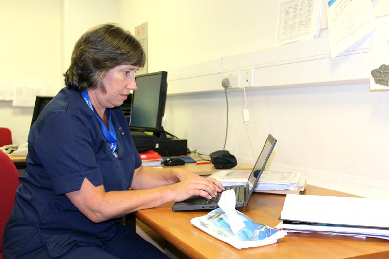 Angela Massey, Cardiff West Community Midwifery Team Leader, using a mobile device to log in patient details