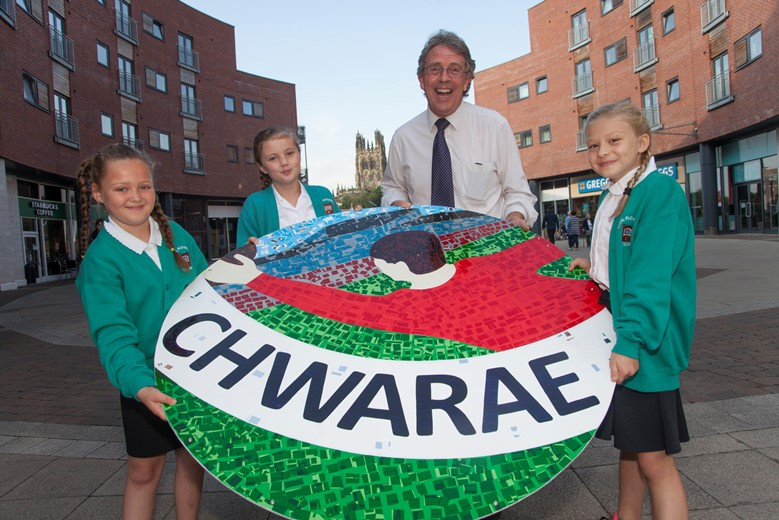 EAGLES MEADOW WREXHAM ... Kevin Critchley presenting  Leah Burke, Luci  Jones and Maya Ratajewska, Pupils  from Ysgol Alexandra  with a piece of the Mural that they had created.