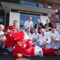 VILLAGE BAKERY WREXHAM AND WFC... Pictured with Wrex the Dragon are Stuart Roberts, Wrexham supporters trust with Village Bakery staff Craig Herling, Martyn Baker Hughes, John Jones, Anthony Dougherty, Daniel Garcia, and Ianin Lake, Village Bakery Managing Director Robin Jones, Geoff Scott WFC commercial Manger  and Catherine Bletcher from Village Bakery .
