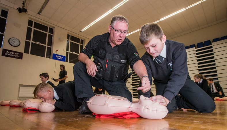 Ysgol Emrys ap Iwan, Abergele. Year 7 & 8 students learning First Aid and how to do CPR in a Restart Heart Campaign. Core Chapman, 11 gets some hints from PC John Wheway