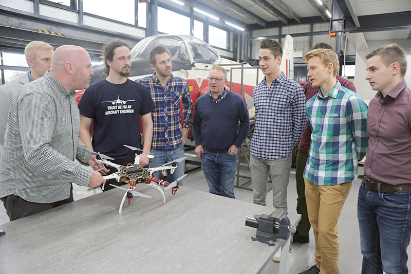Lecturer Nathan Roberts discusses drone technology with Rob Bolam (back, fourth from left) and current engineering students