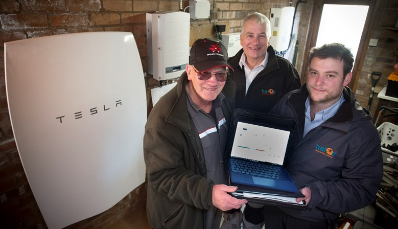 HAFOD RENEWABLES.... retired agricultural contractor Philip Johnson pictured with his new Tesla home battery in his garage with Richard and David Jones of Hafod Renewables.