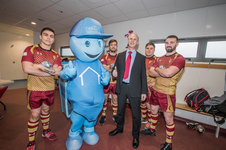 Andrew Bowden, chief executive of Cartrefi Conwy with RGC players to promote the fact Cartrefi is sponsoring the rugby club again. From left, Jacob Botica, Tiaan Loots, Evan Yardley and Afon Bagshaw with Cartrefi Conwy mascot Ty Hapi