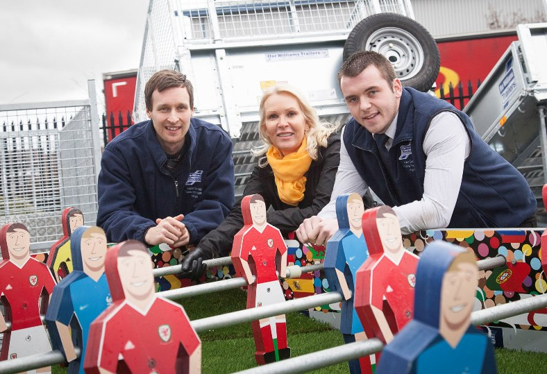 Ifor Williams Trailers have raised £5,000 for Wales Air Ambulance with a football table created from one of their flat bed trailers which was a huge attraction at the Flintshire Eisteddfod. Pictured: Lynne Garlick Fundraising Manager for Wales Air Ambulance along with Ifor Williams Trailers'  Dafydd Gwynedd and Arwyn Evans