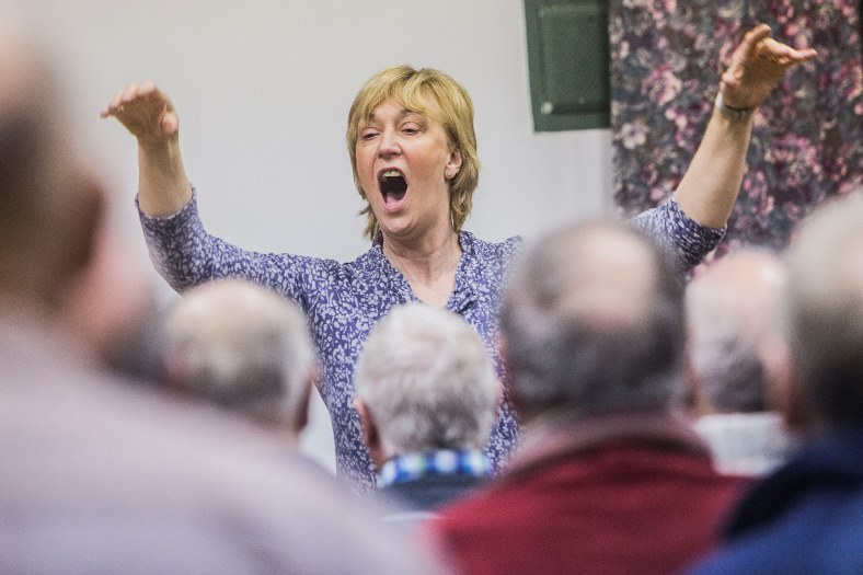 Trelawnyd Male Voice Choir's new conductor, Ann Atkinson, and accompanist Paul Young working with choir.