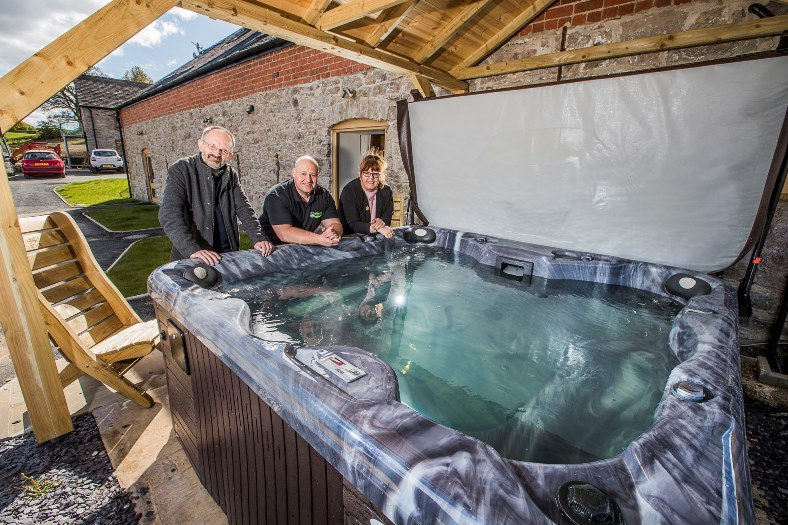 Hot tubs are boosting the income of holiday cottages and pictured at Y Beudy near Pwllglas are David Vasmer, left with Gareth Jones, from UK Leisure Living, and Deborah Nettleton, from North Wales Tourism